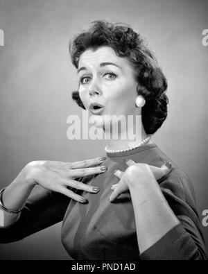 1950s 1960s BRUNETTE WOMAN PEARL STRAND SURPRISED EXPRESSION MAKING WHO ME GESTURE HANDS TO CHEST LOOKING AT CAMERA - g4823 HAR001 HARS LADIES ASKING PERSONS EARRINGS B&W MINE EYE CONTACT BRUNETTE ME HEAD AND SHOULDERS STYLES QUESTION HOUSEWIVES OCCUPATIONS WHO FAUX STYLISH STRAND COSTUME JEWELRY DENIAL FASHIONS MID-ADULT MID-ADULT WOMAN NAG BLACK AND WHITE CAUCASIAN ETHNICITY HAR001 OLD FASHIONED - Stock Image