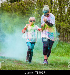 Mother and daughter runners holding hands and being covered in paint on Macmillan cancer charity 5K color fun run. - Stock Image