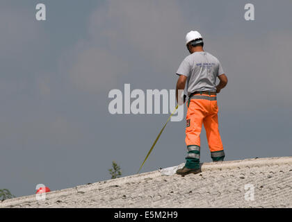 maintenance worker working on rooftop with measuring tape - Stock Image