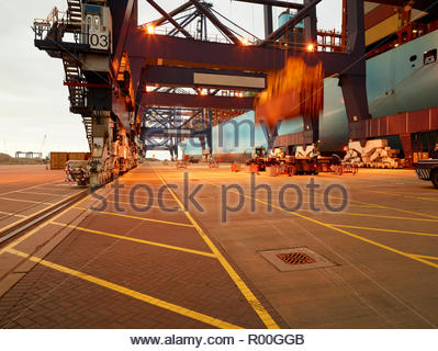 Long exposure of crane unloading cargo container at Port of Felixstowe, England - Stock Image