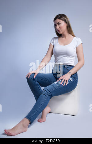 Cute young woman in blue jeans and bare feet sitting on white cube stool in studio and isolated on white blue background. Female fashion portrait - Stock Image