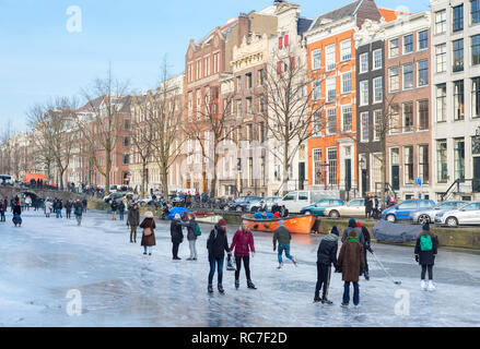 Ice skating people on frozen canal Prinsengracht. Amsterdam, The Netherlands. - Stock Image