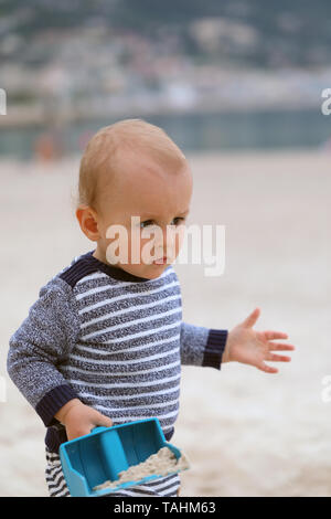 Cute Baby Boy Playing With Sand And Plastic Shovel On The Beach - Stock Image