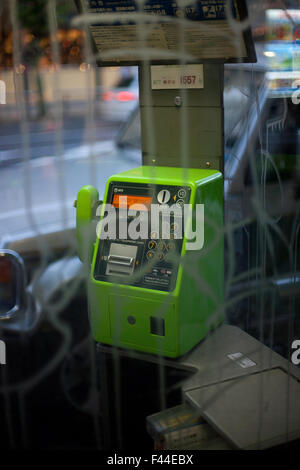 Public pay phone booth with green phone behind vandalized glass - Stock Image