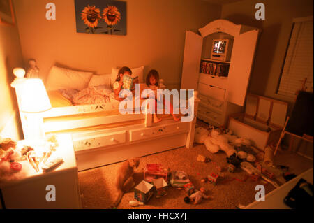 Two young girls in bedroom amid messy sea of toys - Stock Image