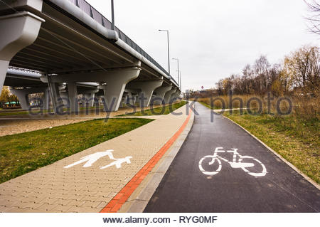 Poznan, Poland - March 3, 2019: Bike route and footpath with symbols along a bridge at a park. - Stock Image