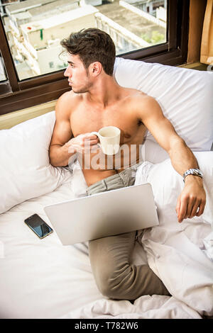 Naked young man with muscular body on bed with mug or cup in hand with coffee or tea, looking at laptop computer screen - Stock Image