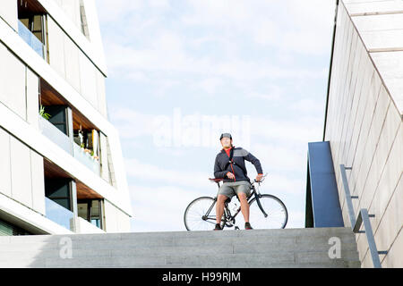 Bike messenger resting on stairway - Stock Image
