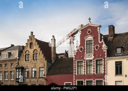 Examples of traditional architecture with large crane in the background, historic city of Bruges, West Flanders, Belgium - Stock Image