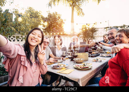 Happy family cheering and toasting with red wine glasses at dinner outdoor - People with different ages and ethnicity having fun at bbq party - Stock Image