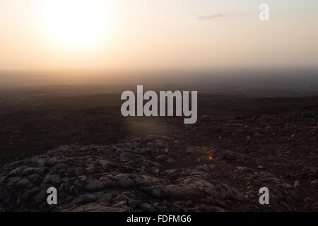 Unexpected intense humidity makes the air around Erta Ale volcano very hazy over the stark black lava fields - Stock Image