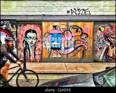A cyclist rides past a row of doors adorned with street art. Are the spray painted pictures fantastic, creative & inspirational? Maybe they are a mess & could be considered property damage? Photo © CH - Stock Image
