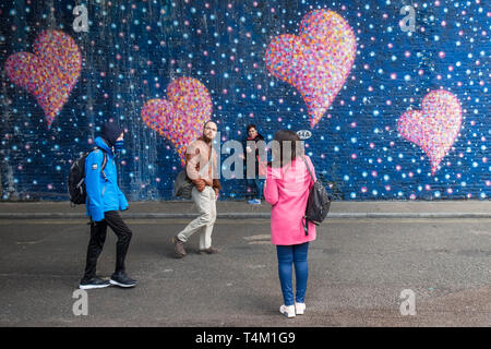 People walking past a large colourful mural painted on a wall in London. - Stock Image