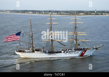 Coast Guard Cutter Eagle transits down the Savannah River towards Savannah, Georgia, Mar. 15, 2019, in front of the Tybee Island Lighthouse. The Eagle arrived in Savannah for St. Patrick's Day weekend with over 100 guests on board. - Stock Image