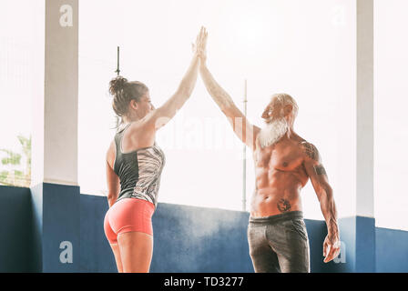 Fitness couple stacking hands in gym wellness club - Happy athletes motivating each other - Stock Image