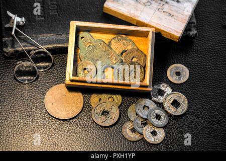 Young boy's balsa wood box 'Keep out' 'Old Coins' full of ancient China and Japan bronze, metal cash coinage-with patina of age. - Stock Image