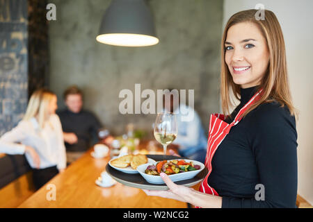 Young woman as a friendly waitress serves appetizers in the restaurant - Stock Image