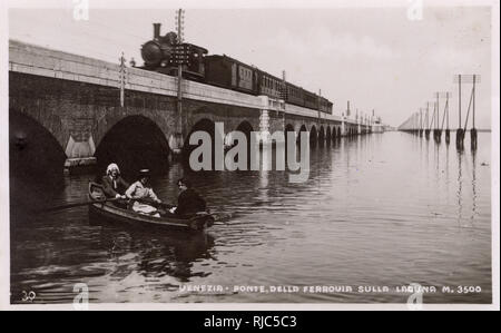 Venice, Italy - Ponte dell Ferrouia sulla Laguna - The Railway bridge over the lagoon. Three tourists appear to have got a little lost on their row out from the city. - Stock Image