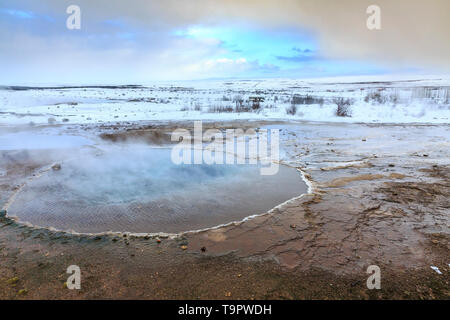 Geothermal landscape Strokkur Geysir in Winter. Located on the Golden circle, Geyir is a popular attraction for tourists. - Stock Image