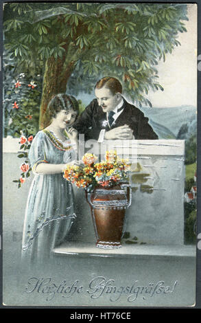 GERMANY - CIRCA 1919: A postcard printed in Germany, shows a couple in love. The inscription in German: Happy Pentecost, - Stock Image