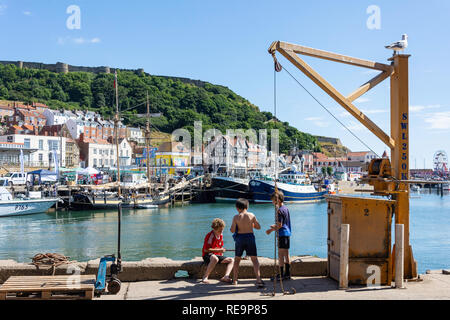 Boys fishing in harbour, Scarborough, North Yorkshire, England, United Kingdom - Stock Image
