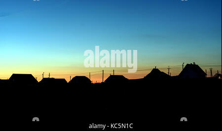 Roof lined village houses in silhouette against a dusk sky of fading blue light - Stock Image