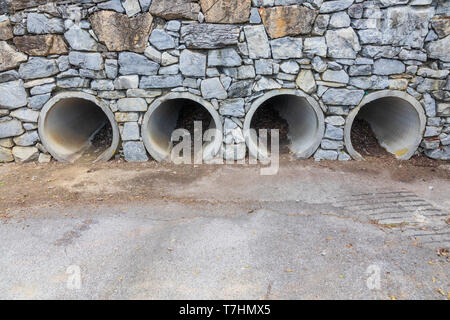 Four large pipes functioning as culverts through a rock wall, opening onto concrete parking lot. - Stock Image