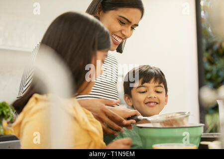 Mother and children baking in kitchen - Stock Image