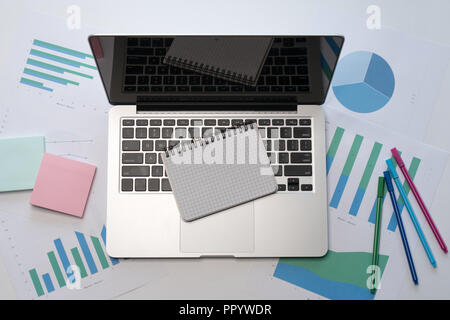 Blank notepad over computer on office desktop with diagrams. Top view with copy space. - Stock Image