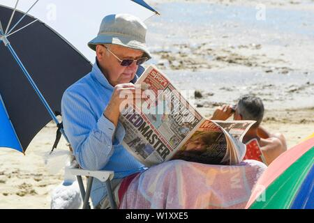 Lyme Regis, Dorset, UK.  4th July 2019. UK Weather.  A man reading a newspaper on the beach at the seaside resort of Lyme Regis in Dorset enjoying a day of clear skies and scorching hot sunshine.   Picture Credit: Graham Hunt/Alamy Live News - Stock Image