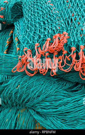 Close up of green fishing nets with a contrasting orange coloured element, Brancaster Staithe, North Norfolk, UK - Stock Image