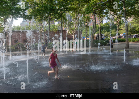 Children playing in a circular stone fountain with 35 in-ground illuminated jets, the Battery Bosque Park, Manhattan, New York - Stock Image