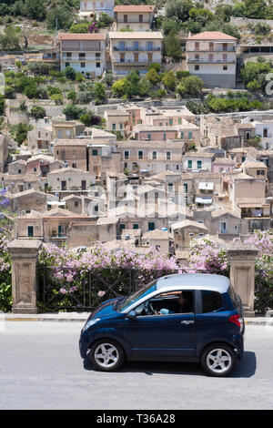 Compact blue small city car in the hill city of Modica Alta famous for its Baroque architecture, South East Sicily - Stock Image