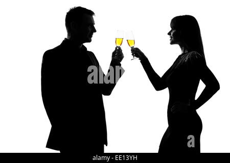 one caucasian couple man and woman drinking champagne toasting partying in studio silhouette isolated on white background - Stock Image