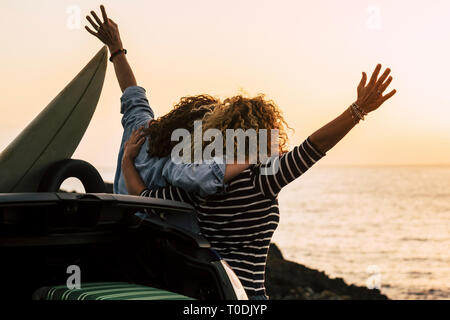 Happy couple of curly girl have fun together and look at the sunset in front of the ocean in tropical beautiful vacation outdoor - hug and friendship  - Stock Image