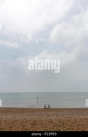 Isolated couple of girls looking the horizon at Hastings Beach, Hastings, East Sussex, England , UK - Stock Image
