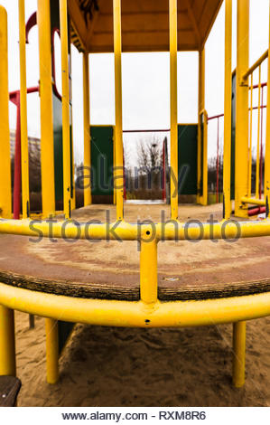 Metal yellow barrier of a climb equipment on a playground. - Stock Image