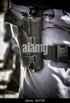 A South African Police Service officer wearing an automatic handgun in a holster in Cape Town at the scene of a - Stock Image