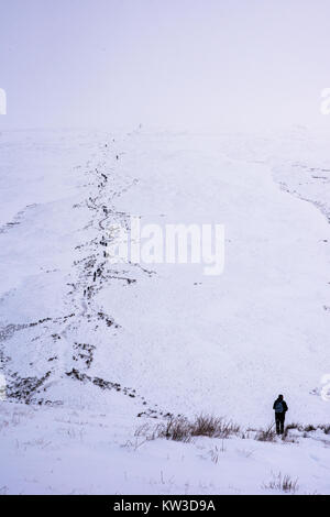 Winter walkers on the path up Pen Y Fan in the Brecon Beacons in South Wales covered in deep snow at Christmas - Stock Image
