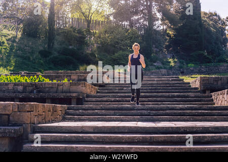 young sporty girl running downstairs in the afternoon on the stairs of the park, morning workout outdoors, sports and healthy lifestyle - Stock Image