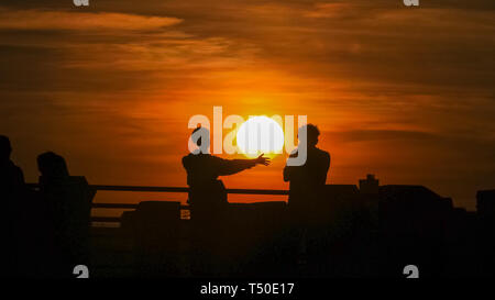 London. 19th Apr 2019. UK Weather: Two people are silhouetted against a beautiful sunset by the River Thames at London's South Bank. Following a day of blue skies and unusually warm temperatures, the rest of the Easter weekend is forecast to see similarly pleasant weather. Credit: Imageplotter/Alamy Live News - Stock Image
