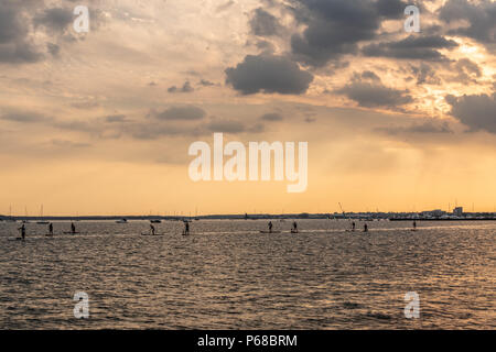 Poole, UK. 28th June 2018. UK weather. The sun sets over Poole Harbour on one of the hottest days on record. Paddleboards get about with just an oar. Credit Thomas Faull / Alamy Live News - Stock Image