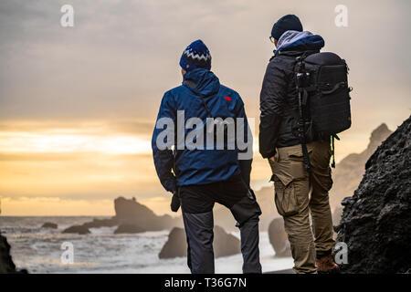 Visitors watching the sunrise in Reynisfjara Beach in Iceland. - Stock Image