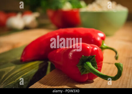 Two red peppers lying on a wooden table - Stock Image