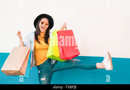 Crazy fashion Asian girl doing shopping in mall center - Happy Chinese woman having fun buying new clothes - Stock Image