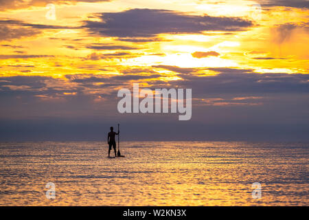 Aberystwyth Wales UK, Tuesday 09 July 2019  UK Weather: A man silhouetted against the colours of the sunset as they paddleboard on the flat calm sea off the beach in Aberystwyth at the end of a warm summers day  in west Wales.   photo credit: Keith Morris//Alamy Live News - Stock Image
