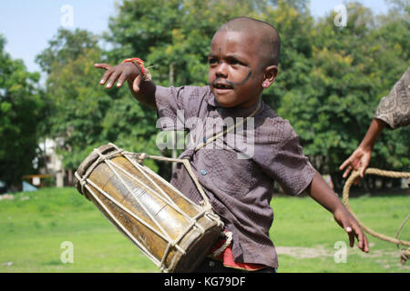 A chld artist plays drums oon the Indian streetside to make a living. - Stock Image