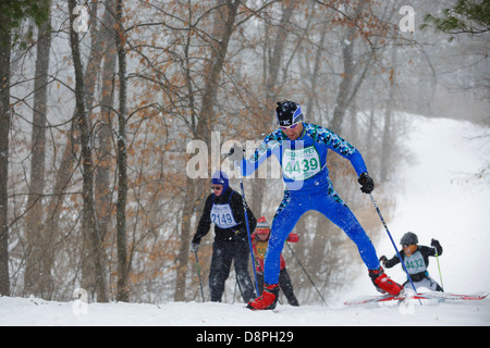 Cross country skiing competitors climb a hill during the Mora Vasaloppet. - Stock Image