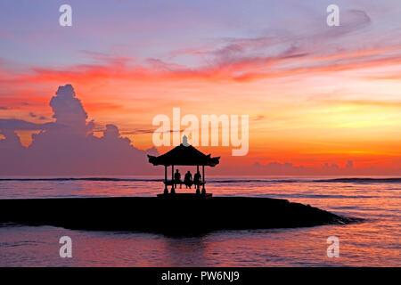 Three people sitting in a Balinese Pagoda on Sanur Beach at Sunrise, Sanur Beach, Bali, Indonesia - Stock Image