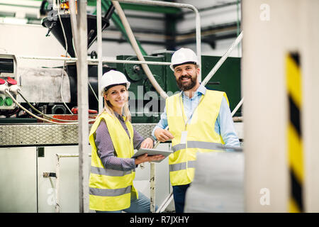 A portrait of a mature industrial man and woman engineer with tablet in a factory. - Stock Image